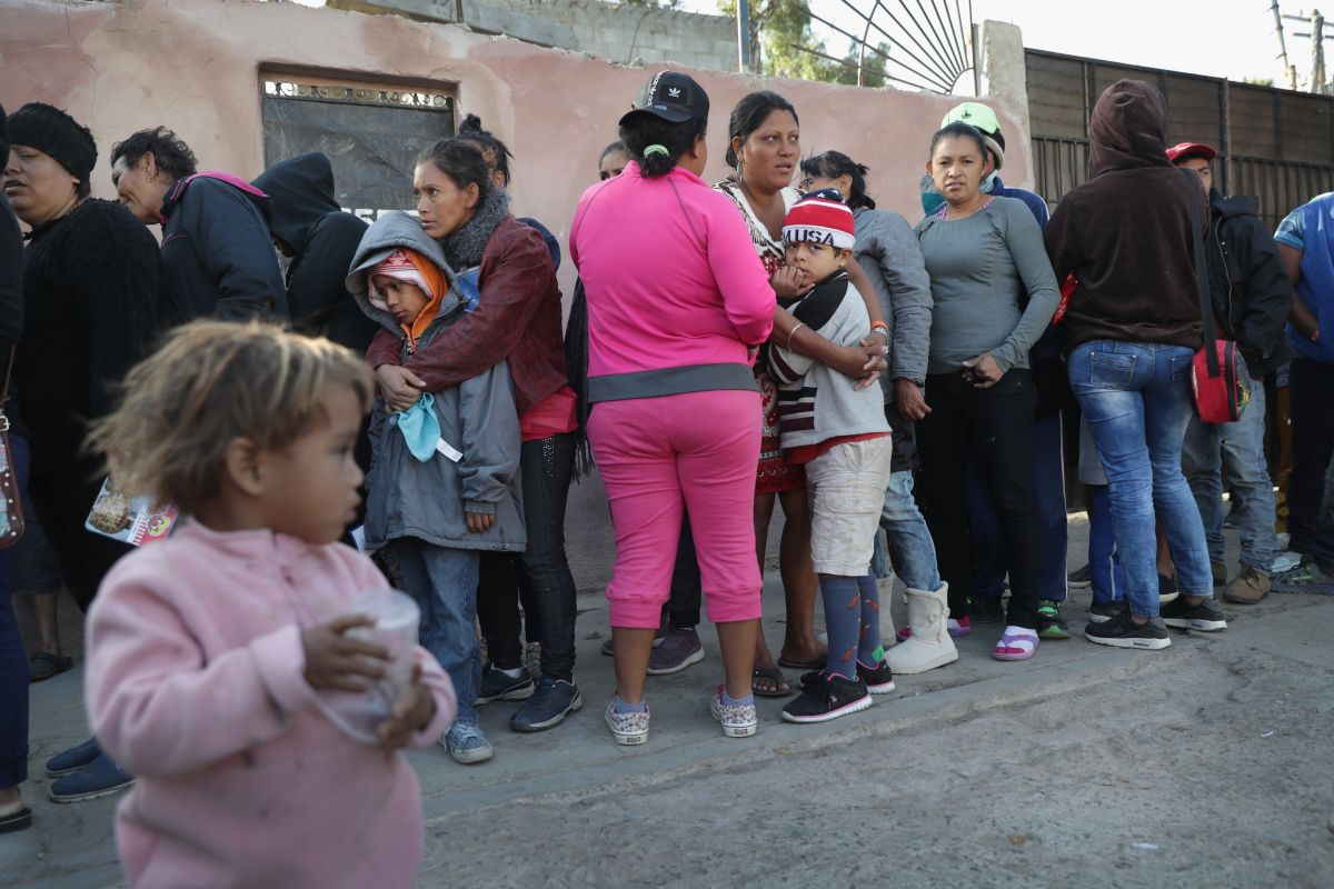 Migrantes esperan por comida en un albergue en Tijuana.