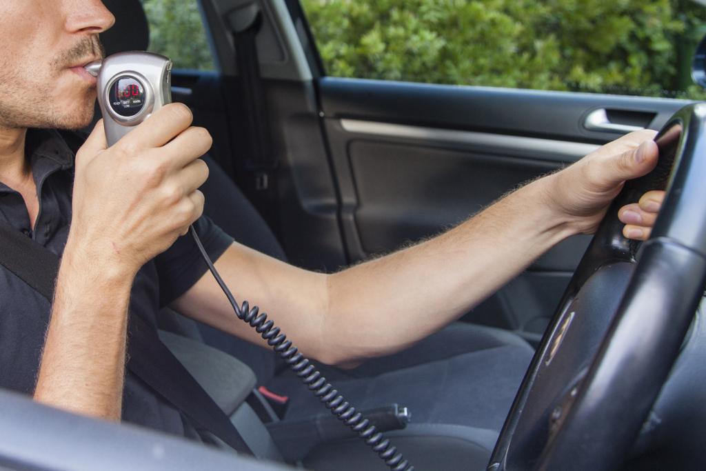 Un hombre sopla en un alcoholimetro antes de encender su auto. (Getty Images)