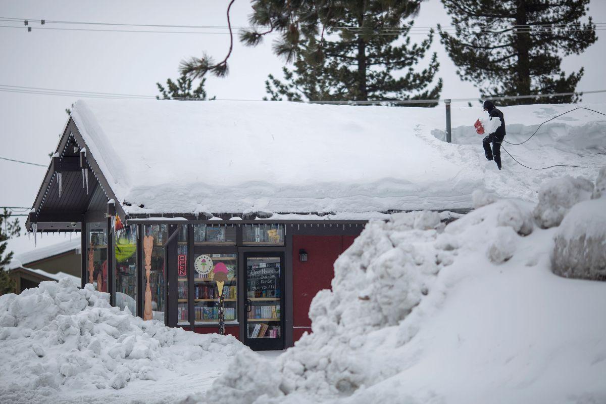 Una persona remueve la nieve del techo de una casa en enero del 2017 cuando una serie de fuertes tormentas de nieve llegó a la zona este de California.