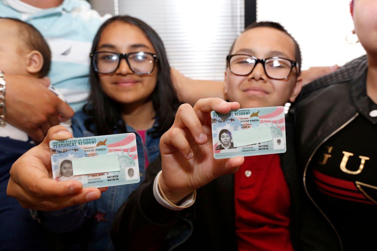 Los menores Arleth y Jose Pocop  muestran contentos sus green cards. / fotos: Aurelia Ventura.