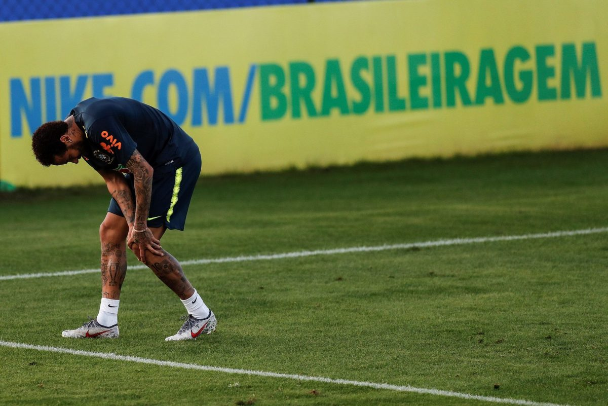 El futbolista brasileño Neymar toca su rodilla izquierda durante el entrenamiento de la selección brasileña.