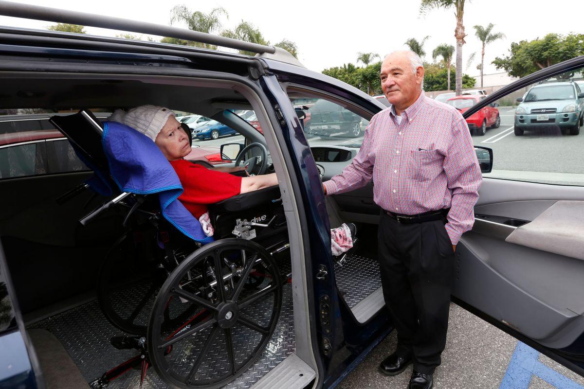 Empleados de Altamed pagan para acondicionar vehículo de una pareja de la tercera edad.  (Aurelia Ventura/La Opinión)