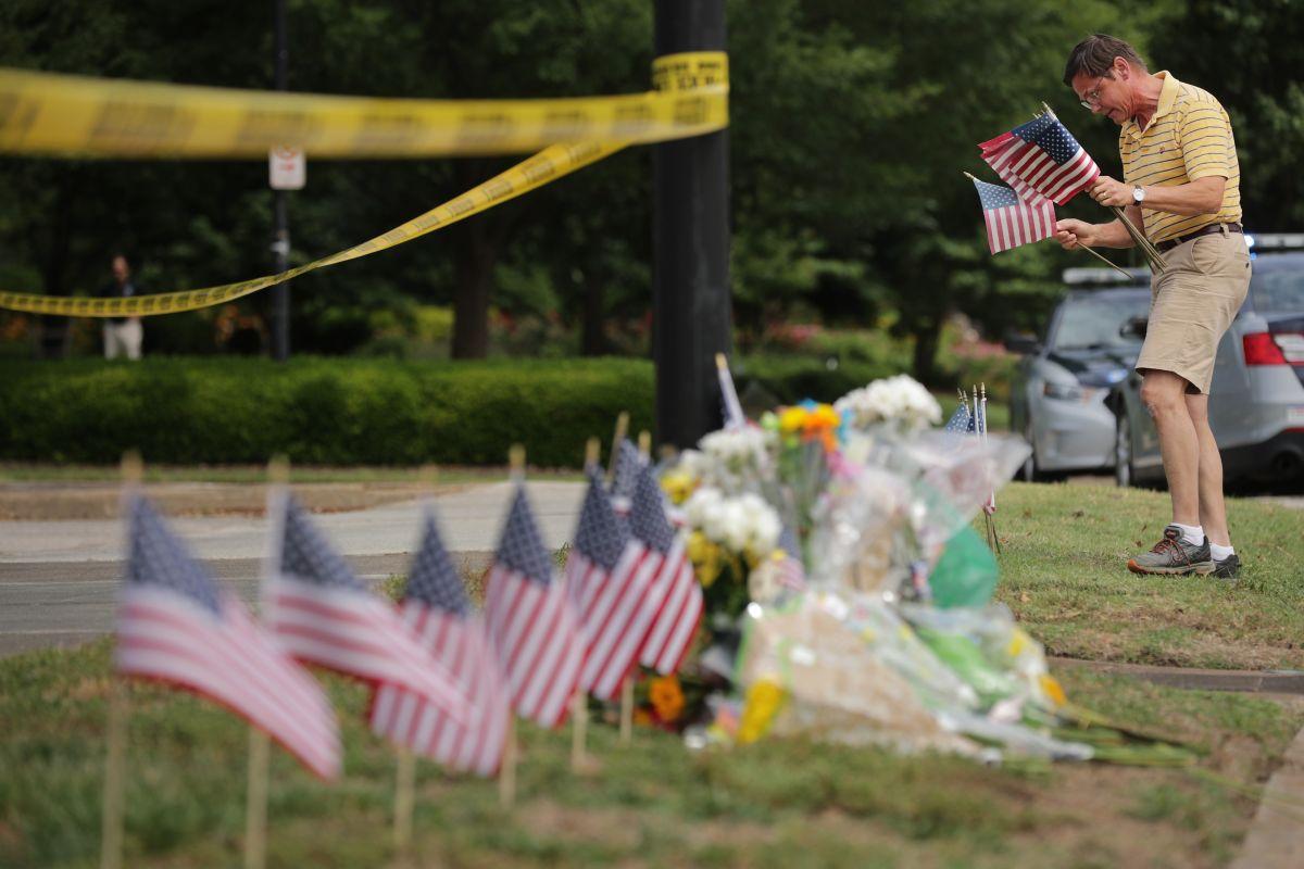 Rich Lindgren coloca 12 banderas en un memorial por los fallecidos.