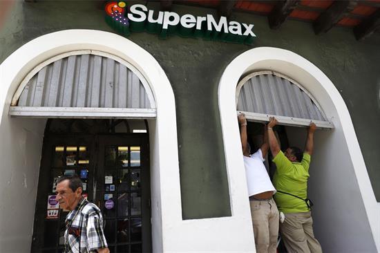 Comerciantes tapan con zinc las puertas de sus negocios en San Juan.
