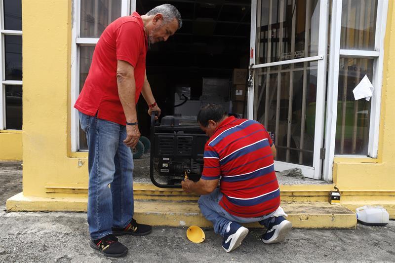 Personas preparan un generador de energía para una casa en Yabucoa, Puerto Rico.