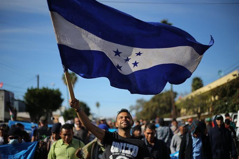 Miembros de una de las caravanas migrantes con la bandera de Honduras.