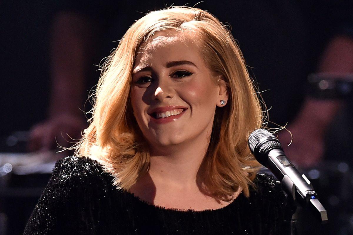 Adele sonriendo en un concierto.