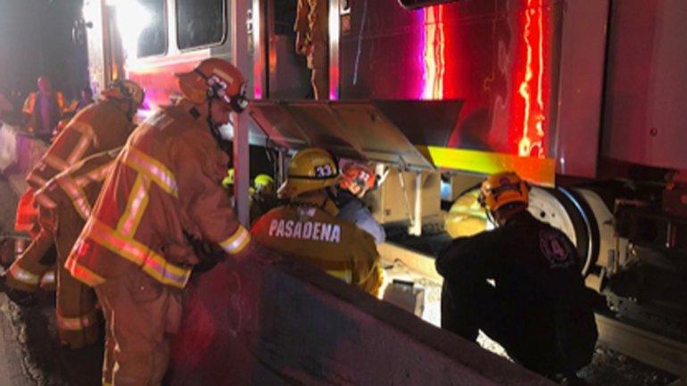 El Departamento de Bomberos de Pasadena trabaja para sacar a una persona atrapada debajo del tren.