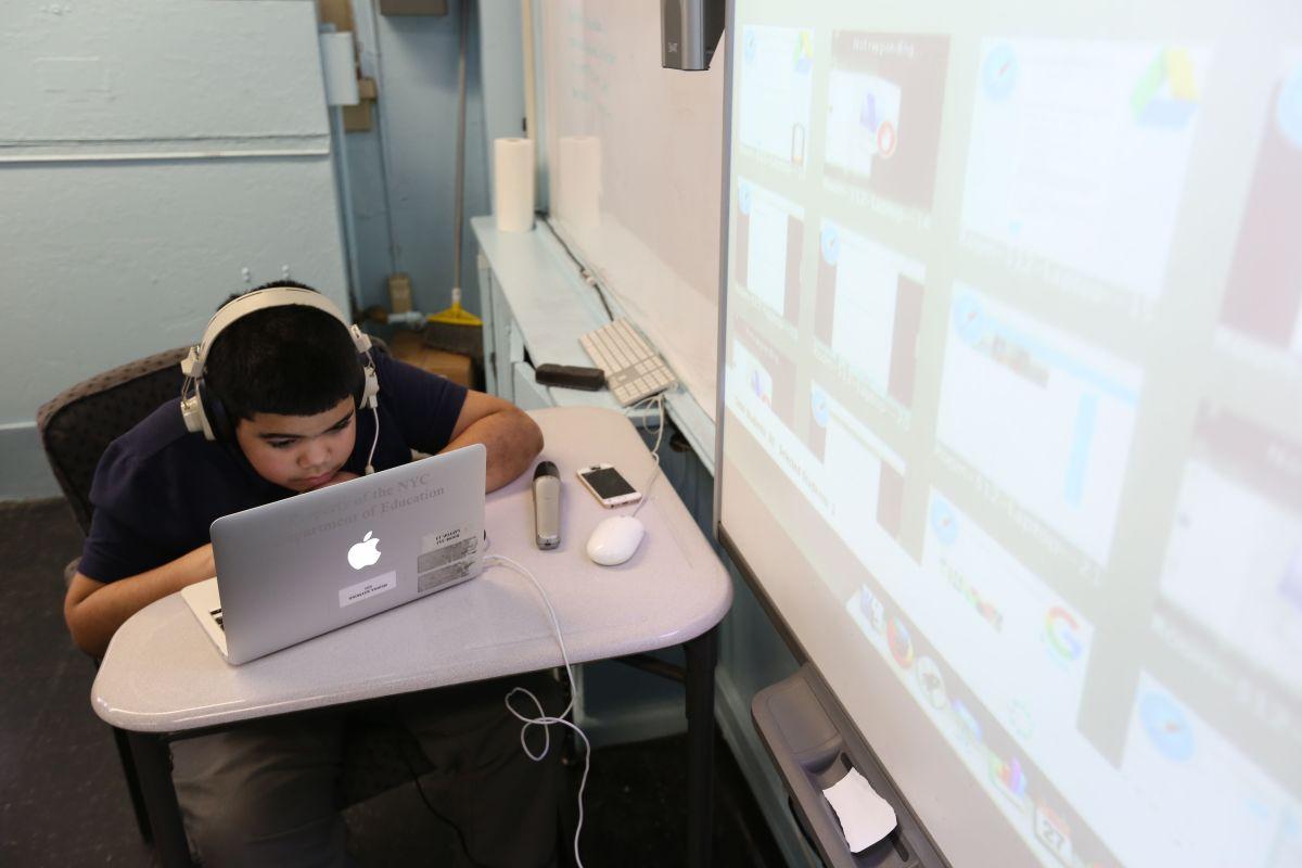 Un joven estudiante utiliza sus recursos electrónicos en un aula de clases.
