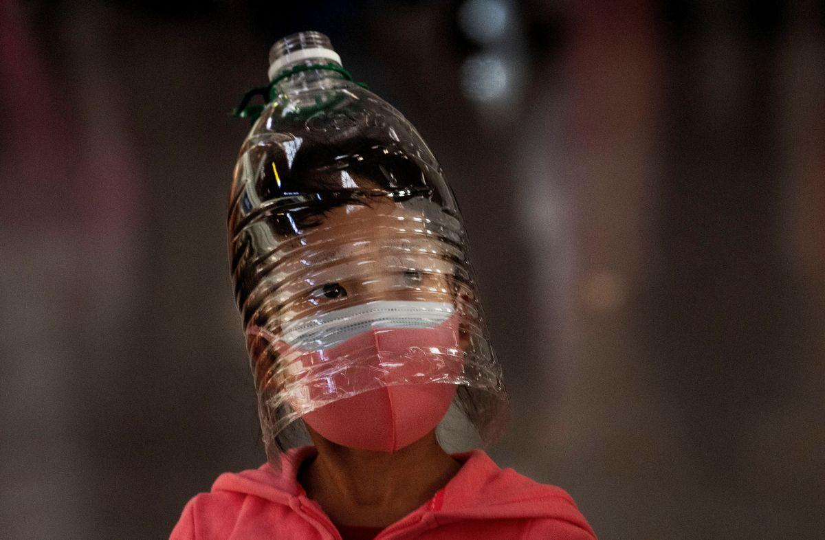 Una menor se protege del coronavirus en el aeropuerto de Beijing.