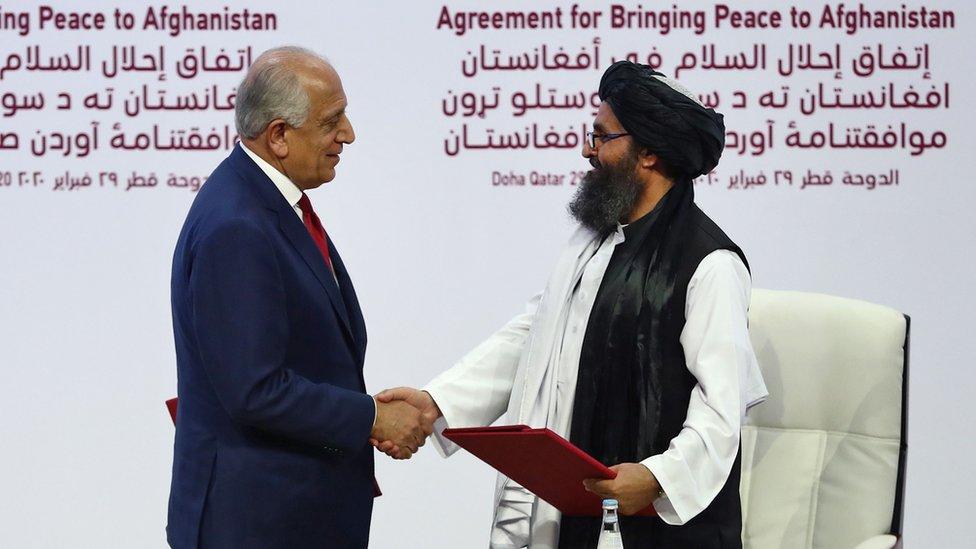 Zalmay Khalilzad da la mano al cofundador del Talibán, Mullah Abdul Ghani Baradar, durante la firma del acuerdo .