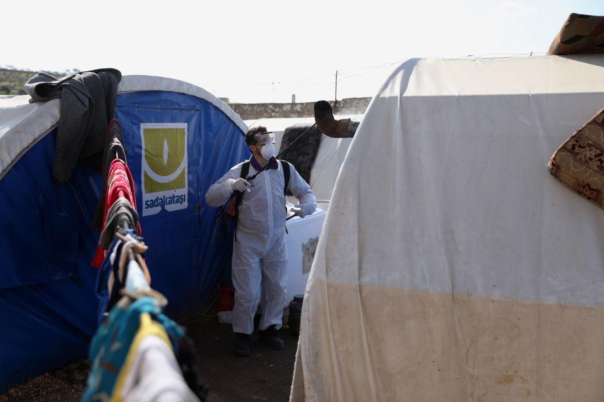 Personal sanitario desinfecta un campamento de desplazados por la guerra.