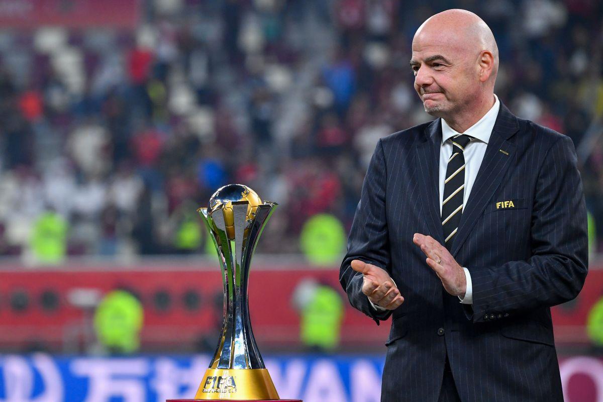 Gianni Infantino, presidente de la FIFA, posa junto al trofeo que se otorga al ganador de la competencia.