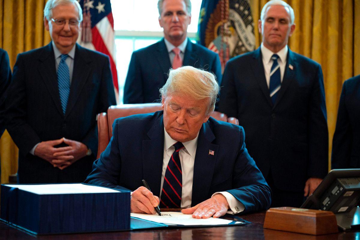 El presidente Trump firma la Ley CARES de estímulo económico.