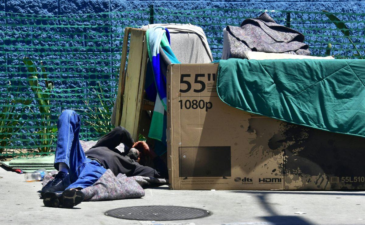 Una persona sin hogar acostada en una calle de Los Ángeles.