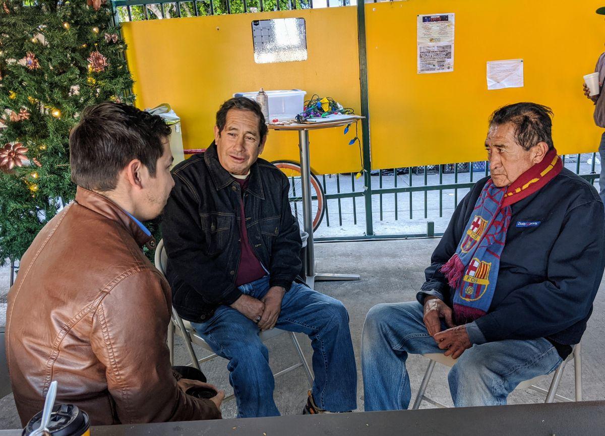 Próspero de León (centro) y Rigoberto Torres (d) en diciembre pasado en el Centro de Jornaleros CARECEN platicaban con el activista pro inmigrante Armando Carmona. (Jacqueline García/La Opinión)