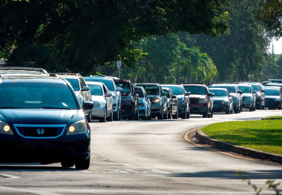 Decenas de conductores esperan en fila para recoger suministros en los Estados Unidos.