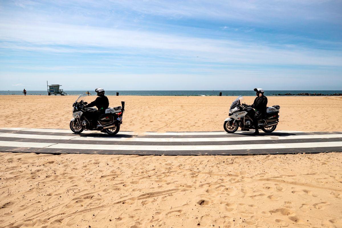 Dos oficiales de la Policía patrullan una playa del condado de Los Ángeles.