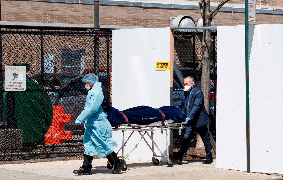 Un médico y un empleado de una funeraria transfieren un ataúd a un coche fúnebre desde una morgue temporal en NY.