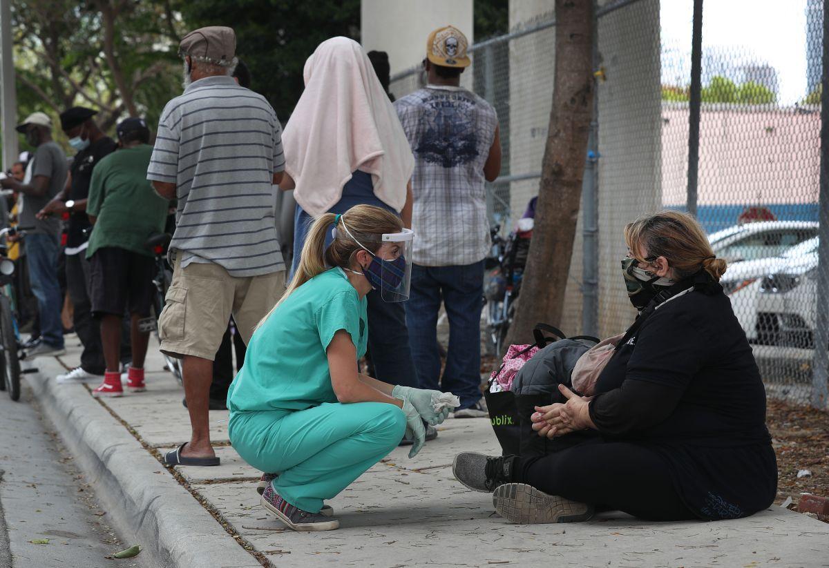 Una enfermera junto a una persona sin hogar en el centro de Miami.