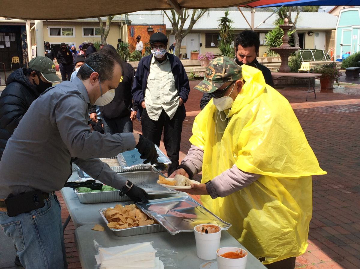Emmanuel Deleage, izq., da de comer a los desamparados del refugio Proyecto Guadalupe. (Suministrada)