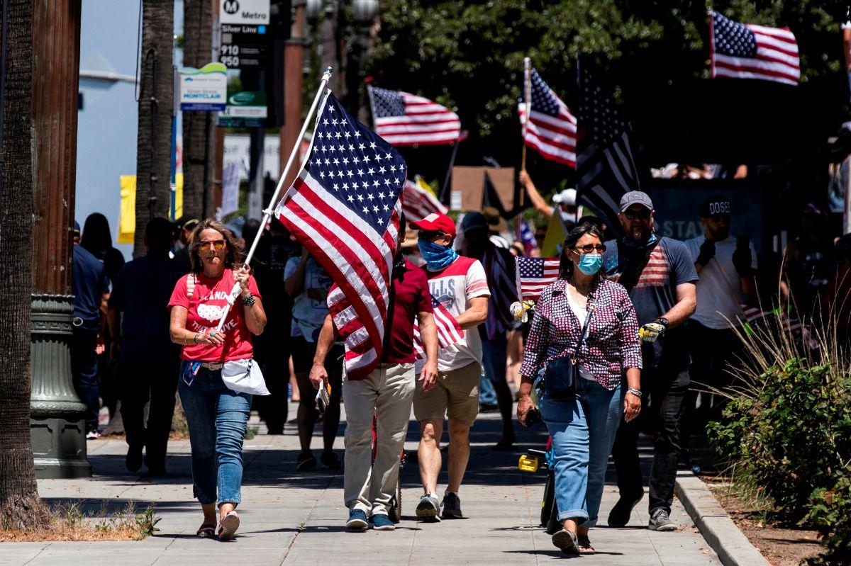 Manifestantes protegidos con mascarillas protestan por el confinamiento en L.A.