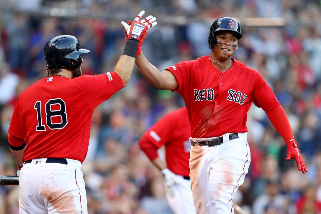 Rafael Devers y Mitch Moreland festejando una carrera con los Boston Red Sox.