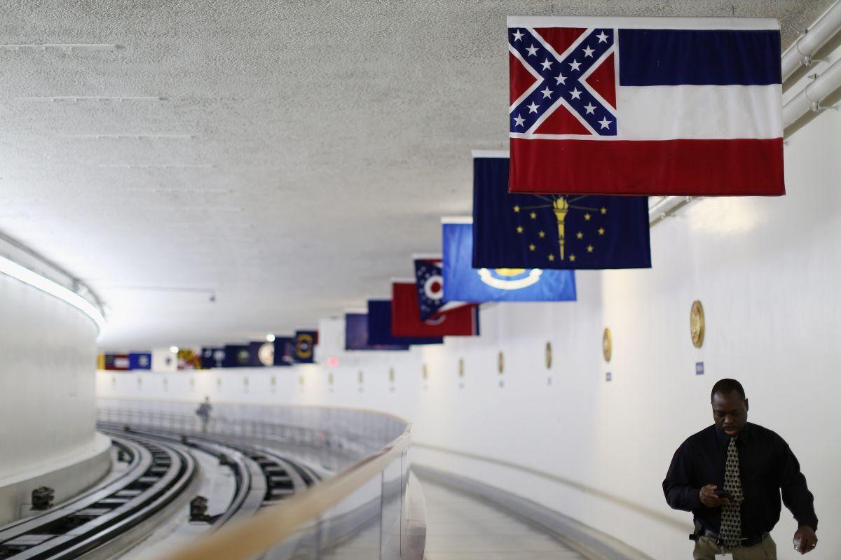 La bandera actual de Mississippi se ve en primer plano, con la bandera confederada en su parte superior izquierda.
