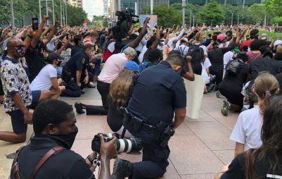 El jefe de la Policía de Houston Art Acevedo (centro) hincado en una de las manifestaciones.