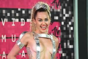 Miley Cyrus mueve su cuerpo usando un body rojo metalizado y medias negras