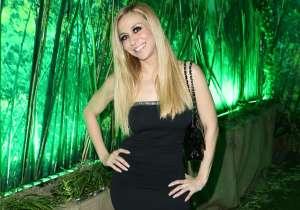 Noelia camina sensualmente hacia la cámara usando un escotado body negro, medias de red y botas altas