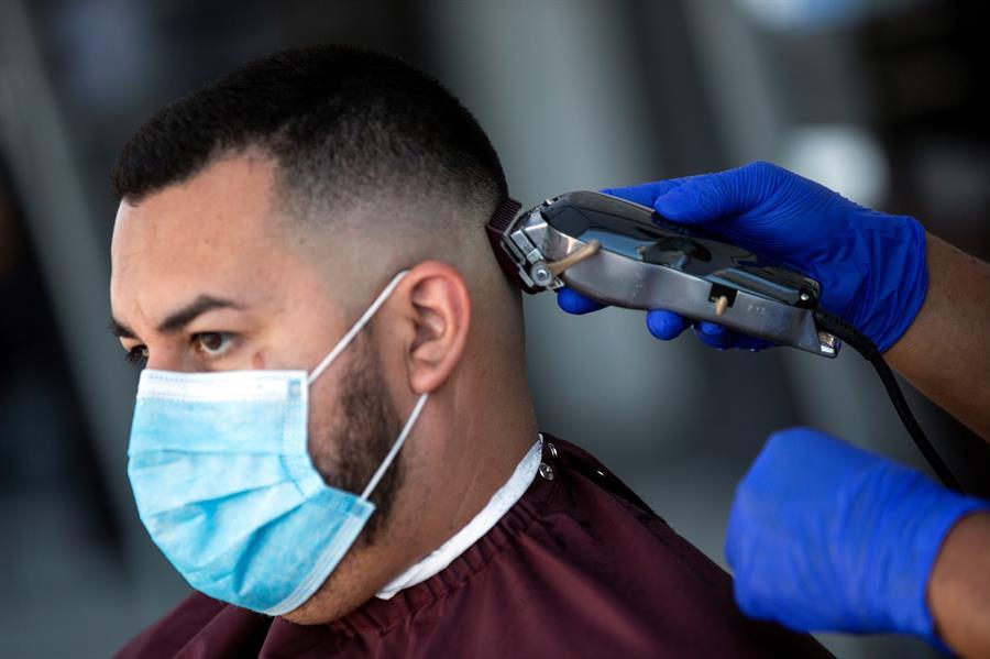 Cliente de una peluquería instalada en un estacionamiento en L.A.