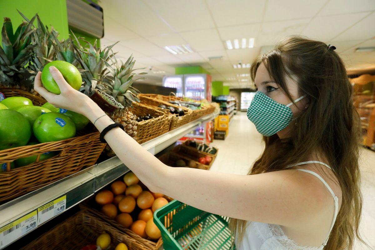 Una mujer usa una mascarilla mientras compra en un supermercado de Bruselas.