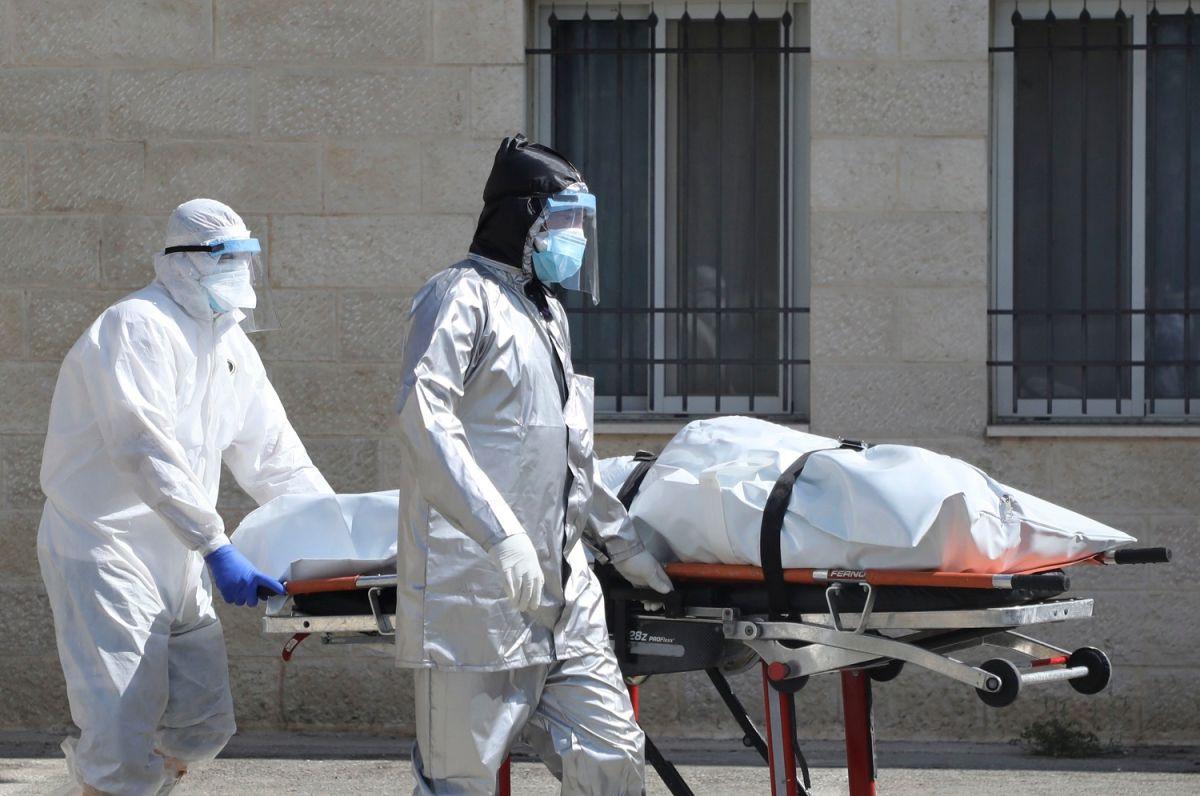 Personal médico transporta el cuerpo de un paciente de coronavirus.
