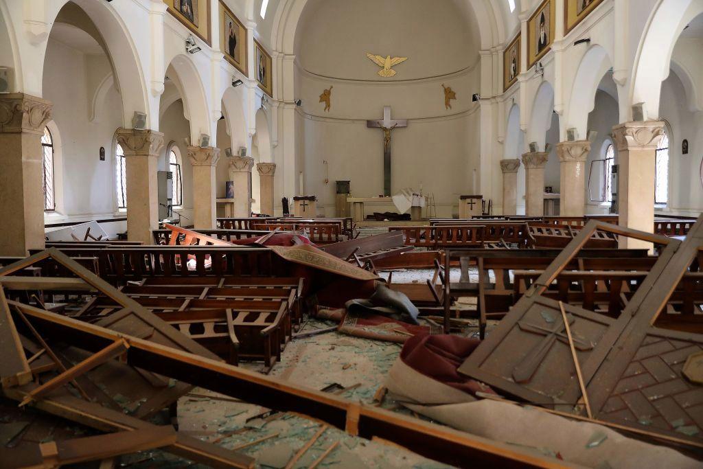 El religioso trata de refugiarse ante el desplome del techo del templo.
