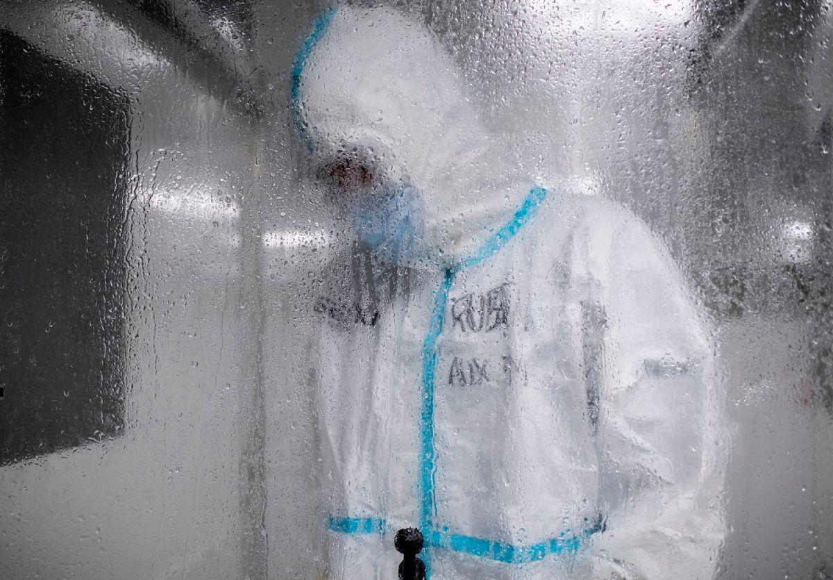 Personal médico se desinfecta luego de trabajar en el área de COVID-19.