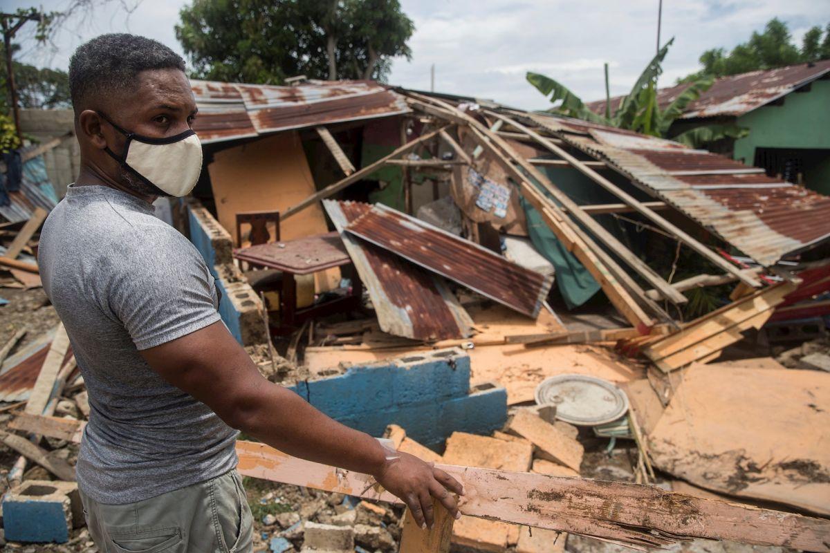 Un hombre intenta reparar su vivienda dañada por el paso del huracán Isaías, este viernes en Hato Mayor (República Dominicana).