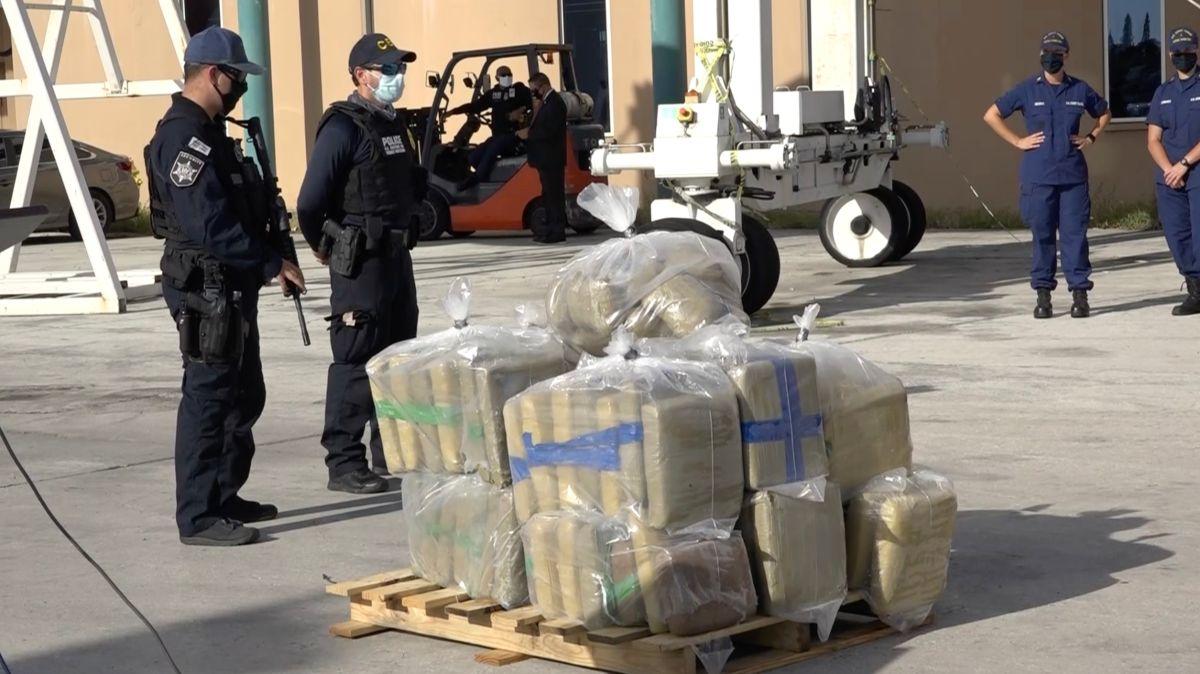 Dos oficiales custodian parte del cargamento confiscado por la Guardia Costera de Estados Unidos.