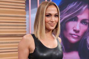 Sobre una mesa y de rodillas, Jennifer Lopez presume sus curvas en un ajustado vestido blanco con aberturas laterales