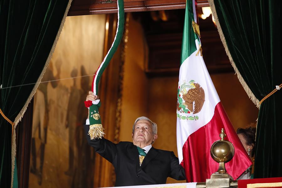 El presidente de México, Andrés Manuel López Obrador, sostiene un cordón con los colores de la bandera mexicana desde un balcón durante la ceremonia del Grito de la Independencia, en el Palacio Nacional de Ciudad de México.