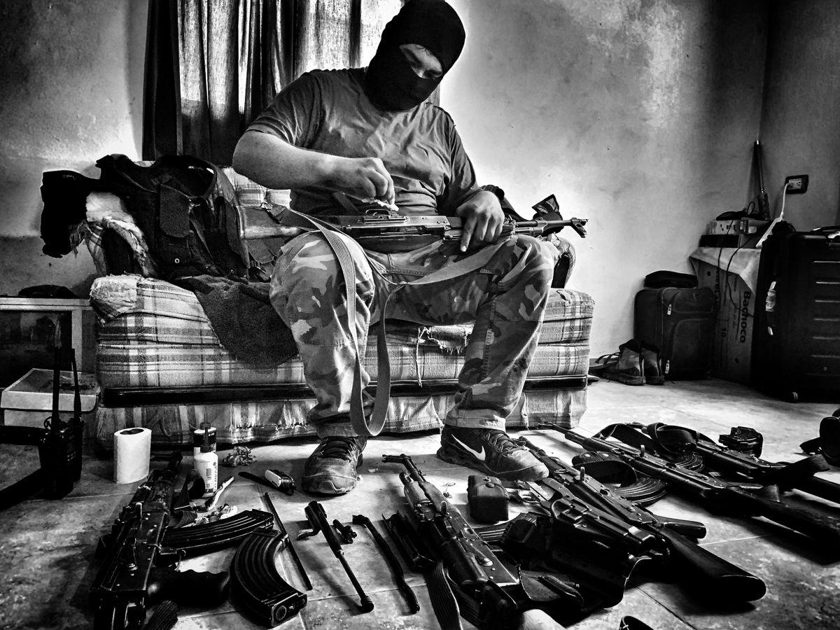 Un miembro del cartel de Sinaloa limpia sus armas.