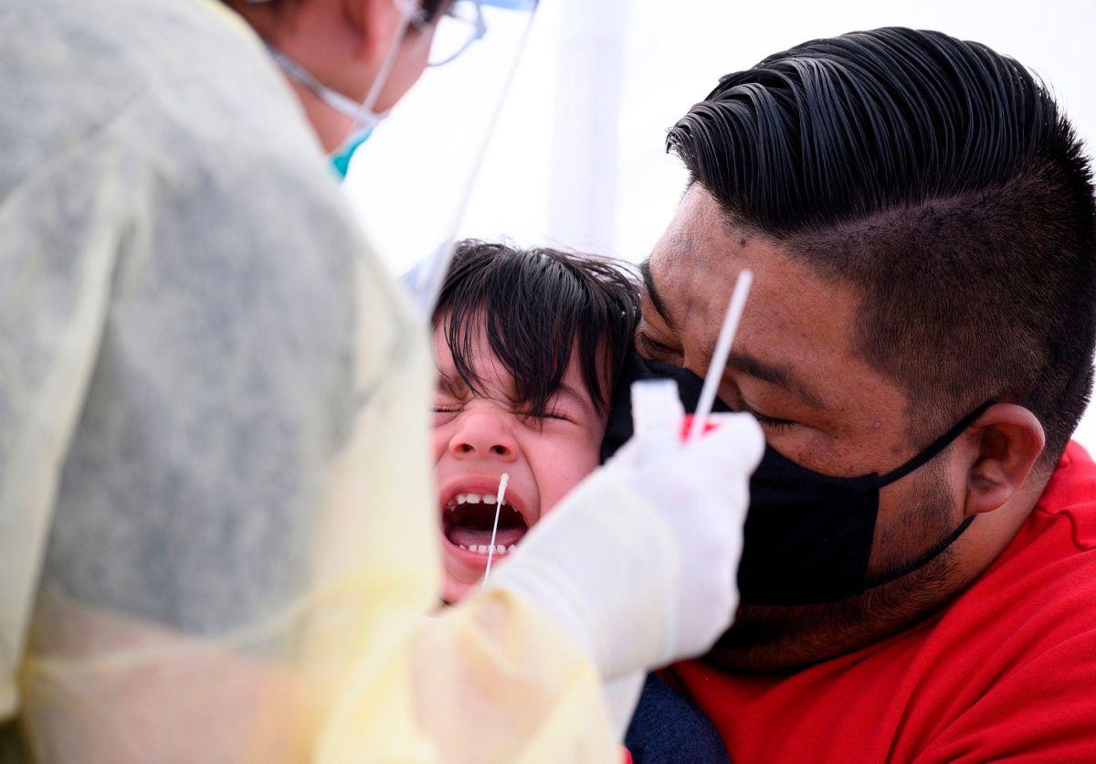 Un padre y un niño hispanos se realizan la prueba de COVID-19 al sur de Los Angeles.