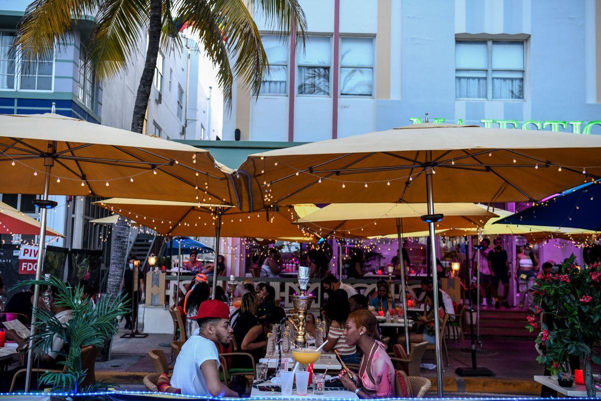 Una pareja disfrutando de unas bebidas en un bar de Miami Beach.