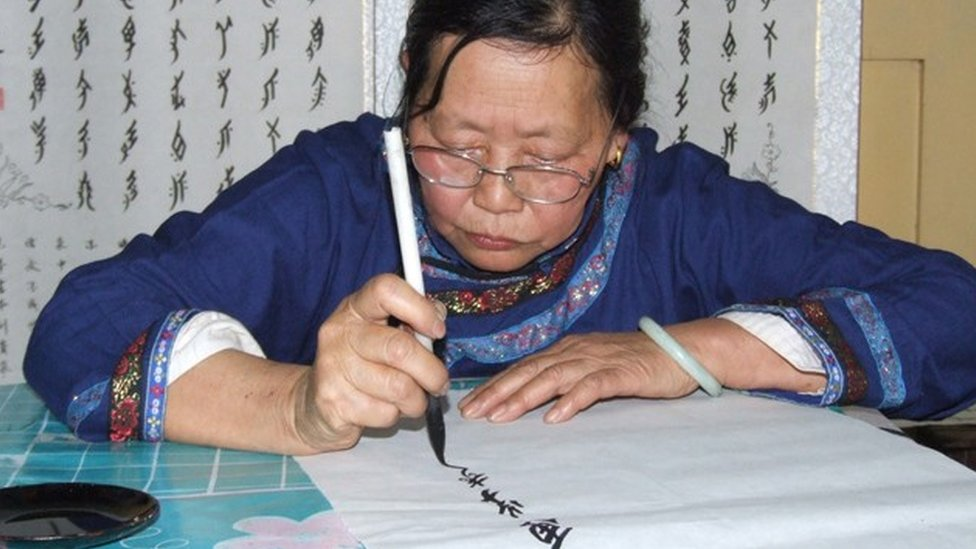 Una mujer dibuja los caracteres de este lenguaje escrito chino exclusivo para las mujeres.