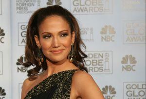 Jennifer Lopez se asoma por una ventana, luciendo su retaguardia en un delgado vestido de seda