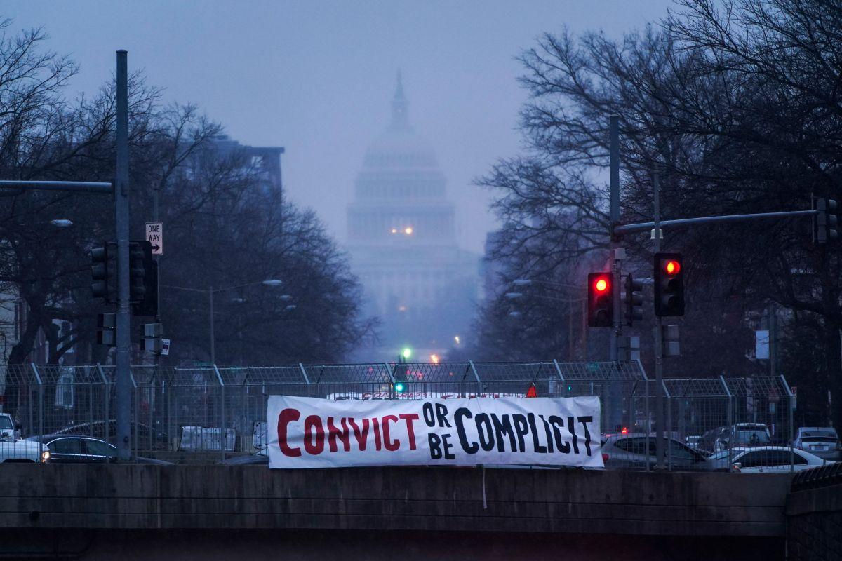 Un letrero que dice 'Condenar o ser cómplice' cuelga de un puente en Washington D.C.