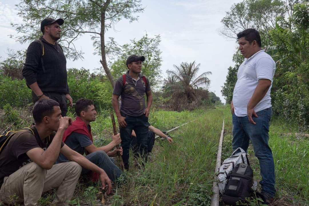 Rubén Figueroa frente a migrantes que esperan el paso del tren en México