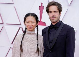 Chloe Zhao llegó con sus acostumbradas trenzas en el cabello y acompañada de Joshua James Richards. Foto: Chris Pizzello-Pool/ Getty Images.