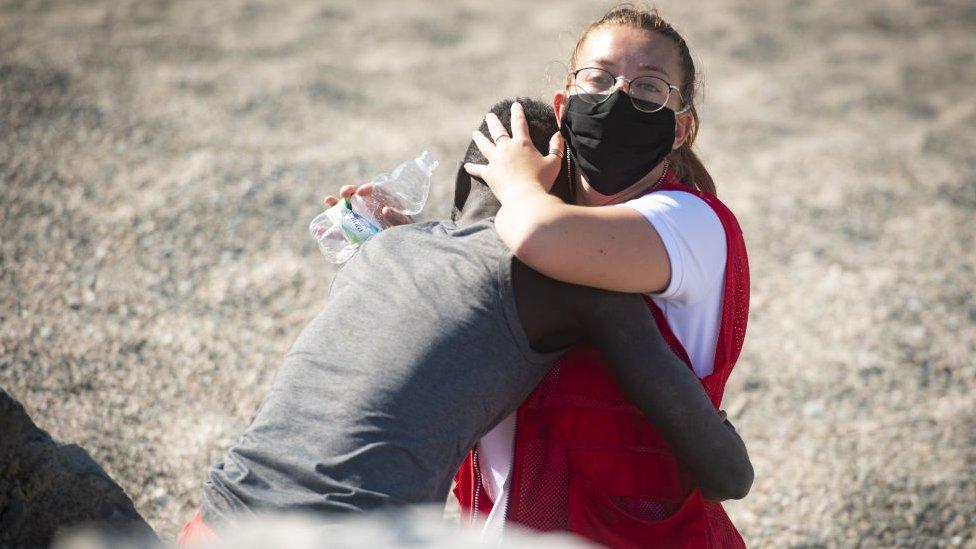 En esta foto, del 18 de mayo, capturada por Marcos Moreno, se ve a Luna Reyes, voluntaria de la Cruz Roja, brindándole ayuda al inmigrante que acababa de salir del mar.