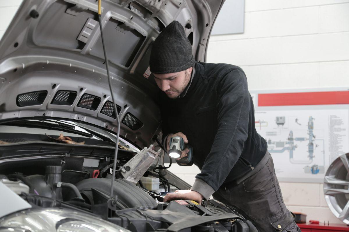 Foto de un mecánico revisando el motor del auto con una linterna